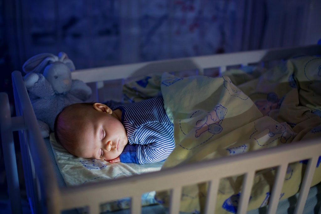Baby sleeping in his crib at night with the lights off