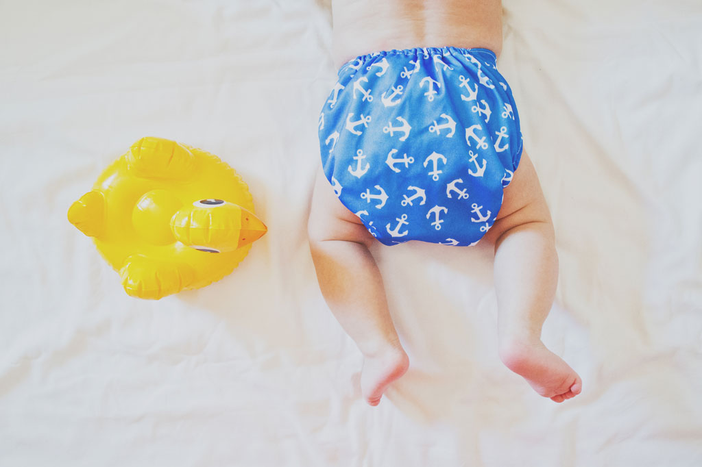 Baby laying down with a blue cloth diaper on him and a rubber ducky